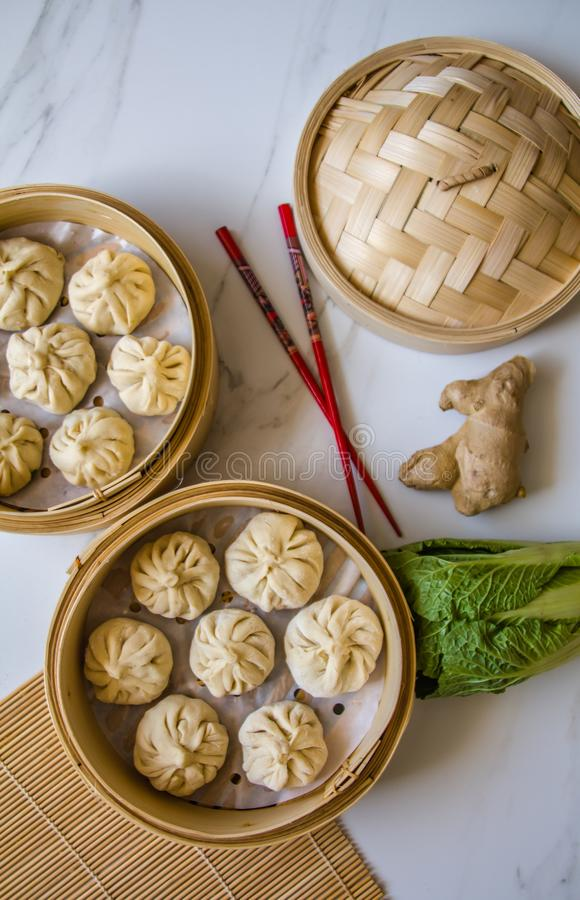 Dim sum aka dumlings,momos in a traditional bamboo steamer, with red chopsticks, Chinese cabbage & ginger root royalty free stock photos