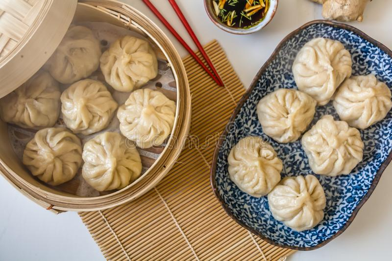 Dim sum aka dumplings,momos in a traditional bamboo steamer, with red chopsticks, Chinese cabbage royalty free stock images