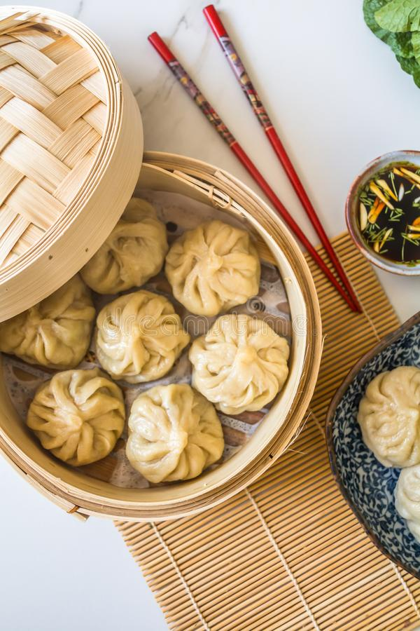 Dim sum aka dumplings,momos in a traditional bamboo steamer, with red chopsticks, Chinese cabbage royalty free stock photos