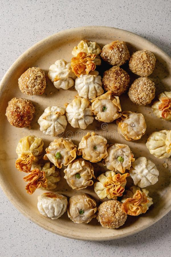 Dim sum party set. Dim sum Gyozas asian fried dumplings party set in ceramic plate over grey spotted background. Flat lay, close up royalty free stock image