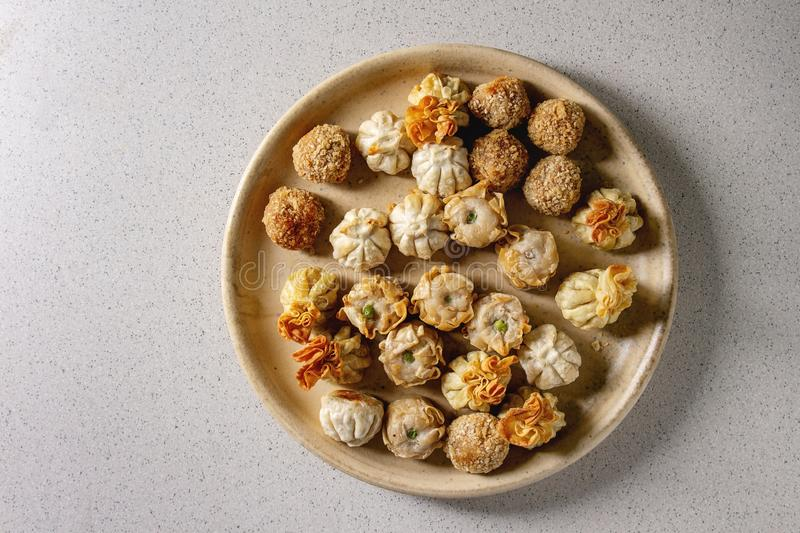 Dim sum party set. Dim sum Gyozas asian fried dumplings party set in ceramic plate over grey spotted background. Flat lay, space stock image