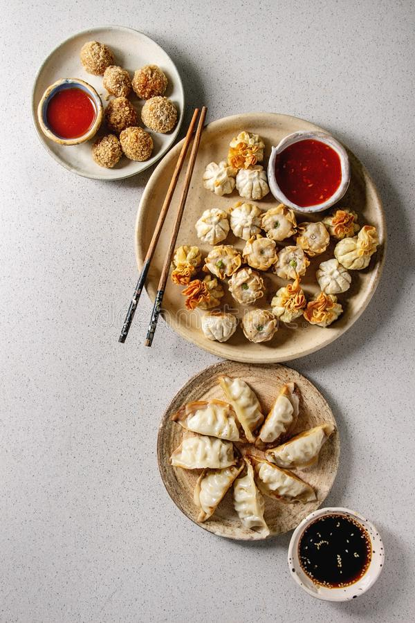 Dim sum party set. Dim sum Gyozas asian fried dumplings party set with variety of sauces served in ceramic plates and bowls with chopsticks over grey spotted stock photography