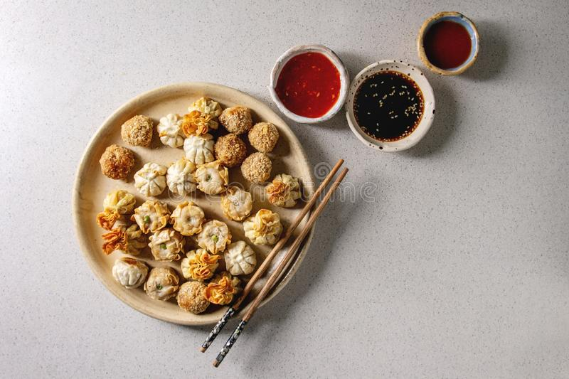 Dim sum party set. Dim sum Gyozas asian fried dumplings party set with variety of sauces served in ceramic plates and bowls with chopsticks over grey spotted stock photo