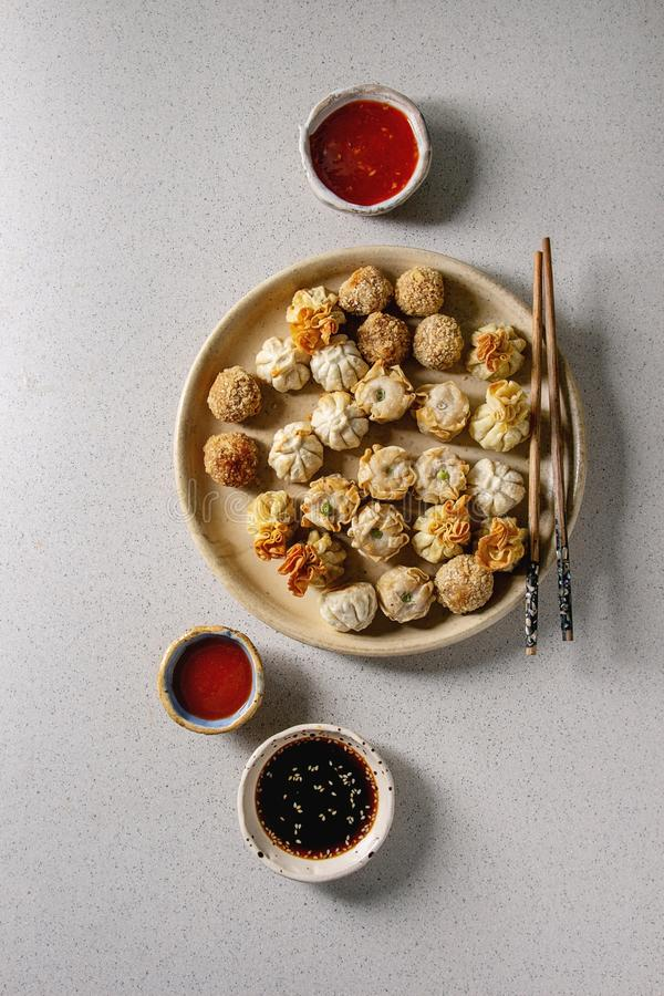 Dim sum party set. Dim sum Gyozas asian fried dumplings party set with variety of sauces served in ceramic plates and bowls with chopsticks over grey spotted stock image