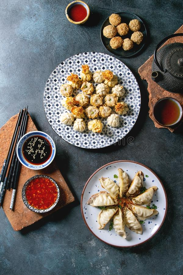 Dim sum party set. Dim sum Gyozas asian fried dumplings party set with variety of sauces served in ceramic plates and bowls with chopsticks, tea cups and teapot royalty free stock image
