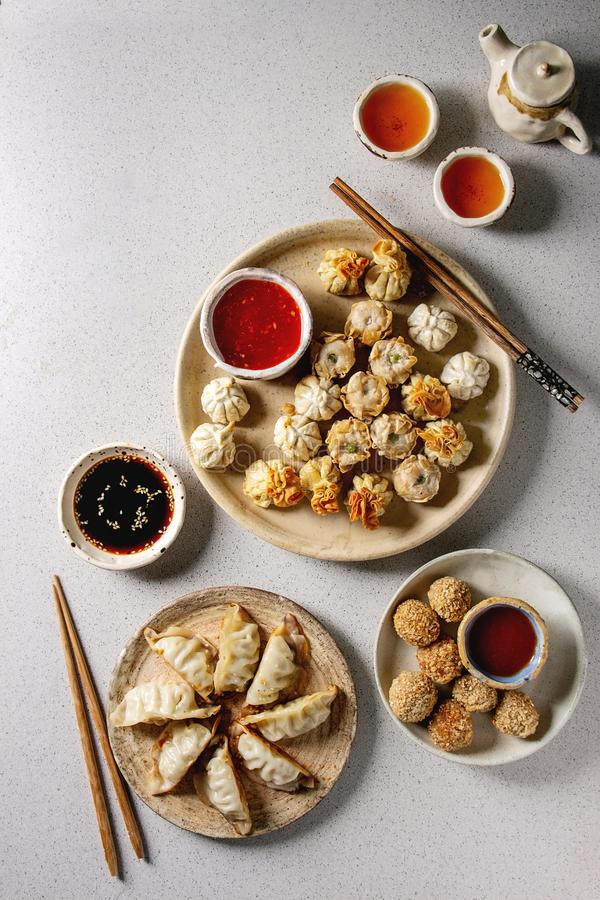Dim sum party set. Dim sum Gyozas asian fried dumplings party set with variety of sauces served in ceramic plates and bowls with chopsticks, tea cups and teapot stock image