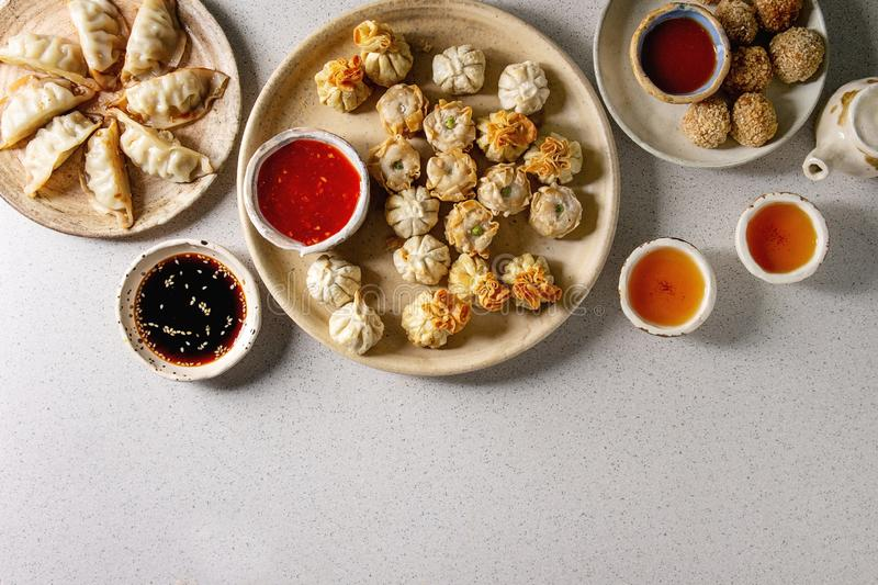 Dim sum party set. Dim sum Gyozas asian fried dumplings party set with variety of sauces served in ceramic plates and bowls with chopsticks, tea cups and teapot royalty free stock images