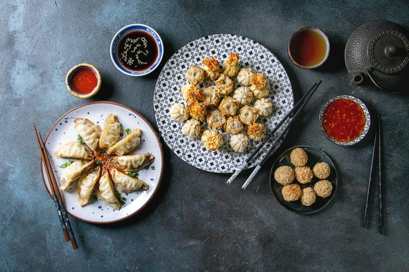 Dim sum party set. Dim sum Gyozas asian fried dumplings party set with variety of sauces served in ceramic plates and bowls with chopsticks, tea cups and teapot stock photography