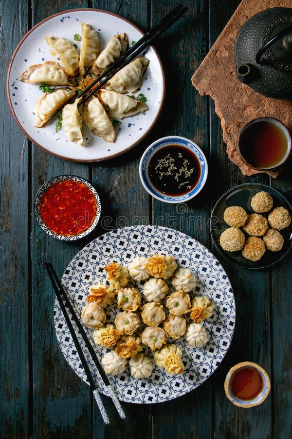 Dim sum party set. Dim sum Gyozas asian fried dumplings party set with variety of sauces served in ceramic plates and bowls with chopsticks, tea cups and teapot royalty free stock photography