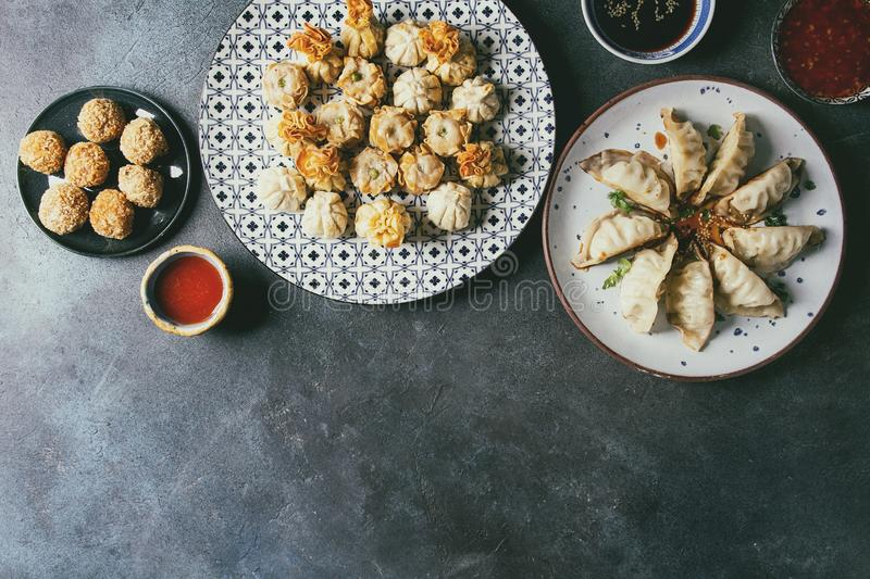 Dim sum party set. Dim sum Gyozas asian fried dumplings party set with variety of sauces served in ceramic plates and bowls with chopsticks, tea cups over dark stock images
