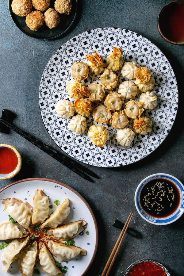 Dim sum party set. Dim sum Gyozas asian fried dumplings party set with variety of sauces served in ceramic plates and bowls with chopsticks, tea cups over dark stock photo