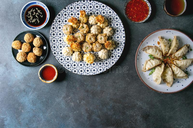 Dim sum party set. Dim sum Gyozas asian fried dumplings party set with variety of sauces served in ceramic plates and bowls with chopsticks, tea cups over dark royalty free stock image