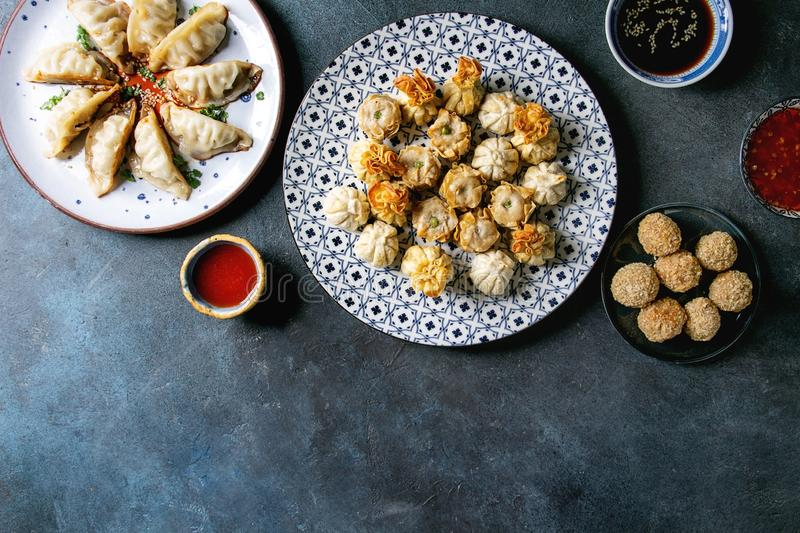 Dim sum party set. Dim sum Gyozas asian fried dumplings party set with variety of sauces served in ceramic plates and bowls with chopsticks, tea cups over dark royalty free stock photos