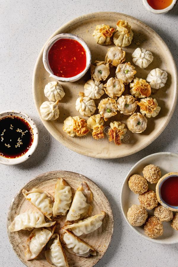 Dim sum party set. Dim sum Gyozas asian fried dumplings party set with variety of sauces served in ceramic plates and bowls with chopsticks, tea cups over grey royalty free stock photography