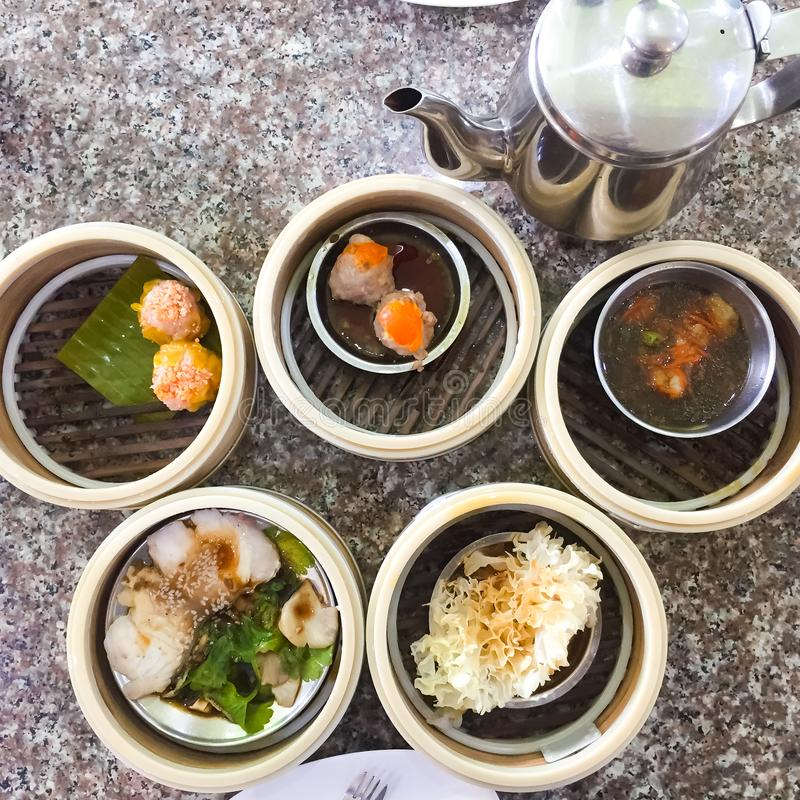 Dim sum , this is a popular Chinese food which were steamed. They are in the small bamboo basket. The picture on the right is the. Tea cup. It is suitable for royalty free stock photo