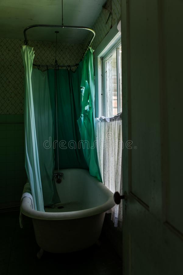Derelict Claw Foot Bathtub + Shower Curtain - Abandoned House in Catskill Mountains - New York. A dim view of a derelict claw foot bathtub and green shower stock images