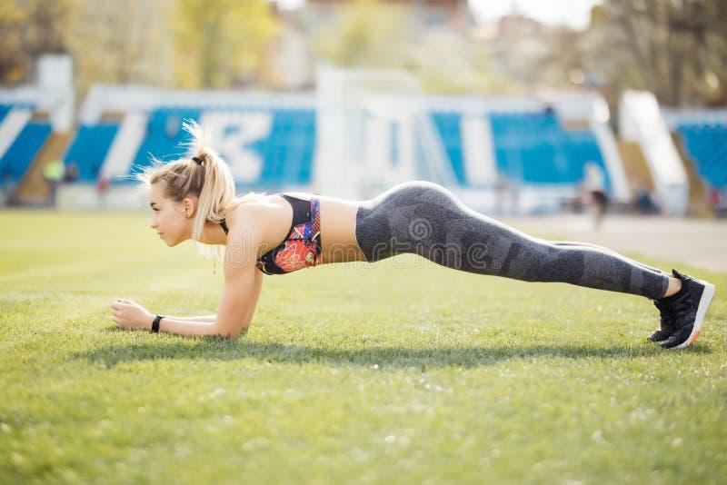 Dimagrisca la donna atletica che fa l'esercizio del tavolato nello stadio su erba verde del campo di football americano, allename fotografia stock