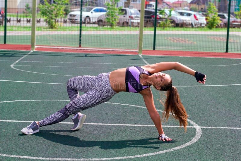 Dimagrisca la donna atletica che fa l'esercizio del tavolato sul campo da pallacanestro immagine stock libera da diritti