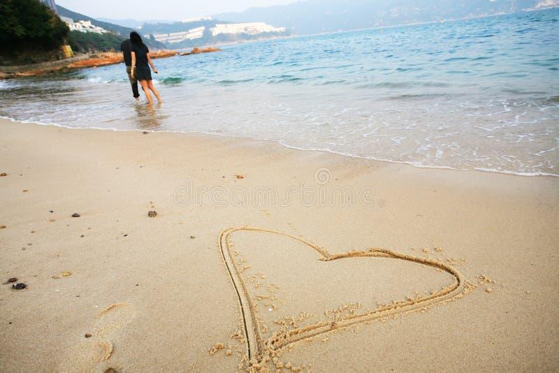 Dimensión de una variable del corazón en la playa imágenes de archivo libres de regalías