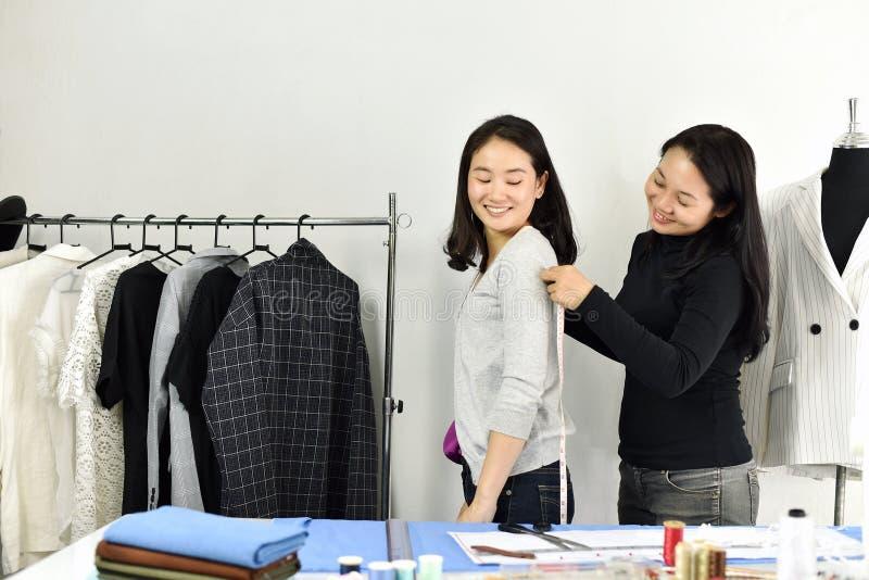 Dimensione corporea del cliente di misure dello stilista con nastro adesivo di misurazione, modello del sarto su misura progettaz fotografie stock libere da diritti