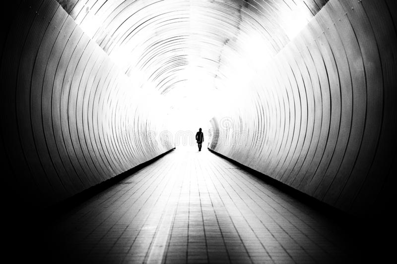 Diminishing perspective of unrecognizable man in a bright public tunnel. In Stockholm, Sweden. The tunnel is a walking path between two streets stock photos