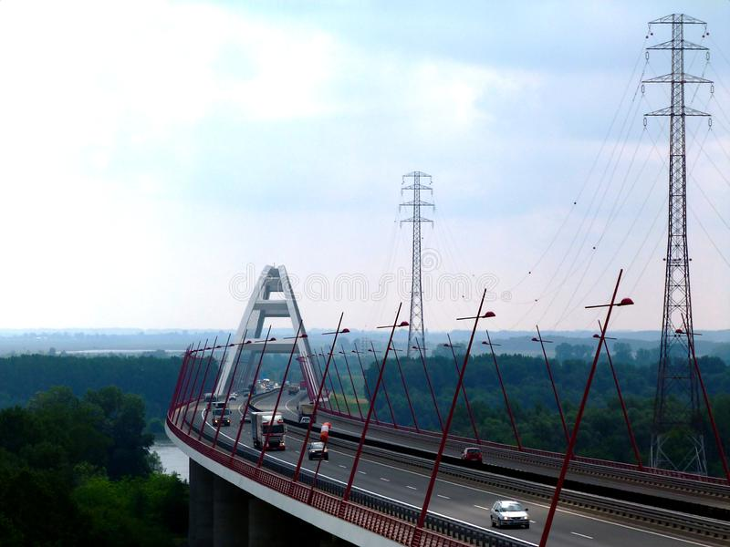 Diminishing perspective view of white basket handle bridge and car traffic. On the highway. deep red leaning steel street lamps leading the eye to the bridge stock photo