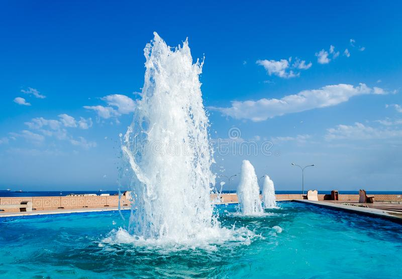 Diminishing Perspective of water fountains against a blue sky royalty free stock photos