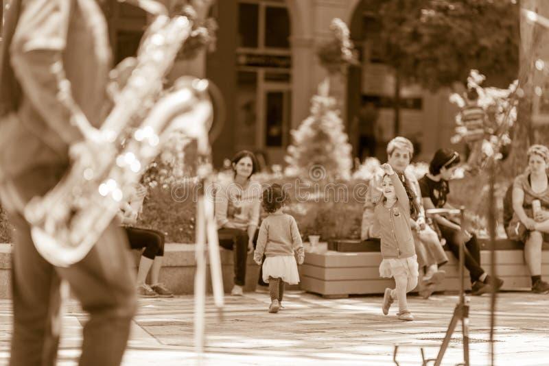 Children dancing to jazz music. DIMITROVGRAD, BULGARIA - APRIL 30, 2018: Two children dancing full of joy at street concert event dedicated to International royalty free stock photos