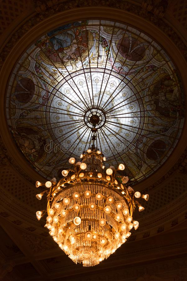 Dimly Lit Renaissance Style Crystal Chandelier with Window Glass Dome stock image