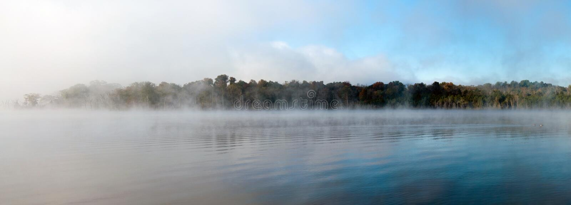 dimmaängmorgon över vatten arkivfoto