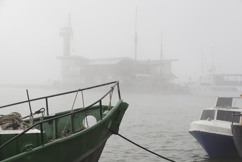 Dimma i hamnstaden Gammal grön fiskebaot arkivfoto