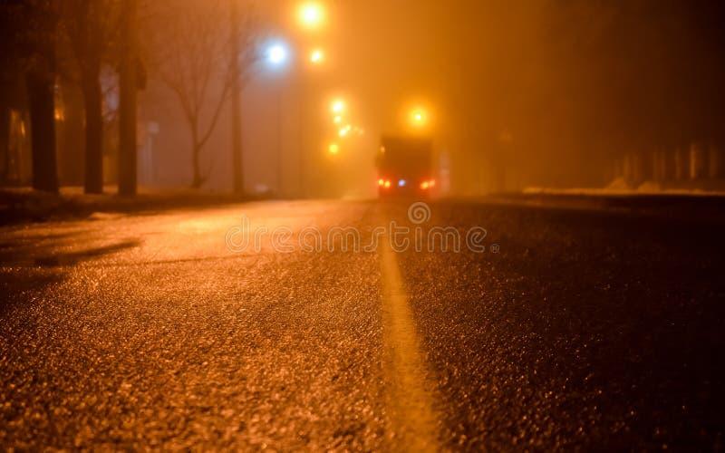 Dimma på gatorna av nattstaden Asfaltera vägen och bilen i dimma våt asfalt, farlig hal väg i vintersäsongen Stre arkivfoto
