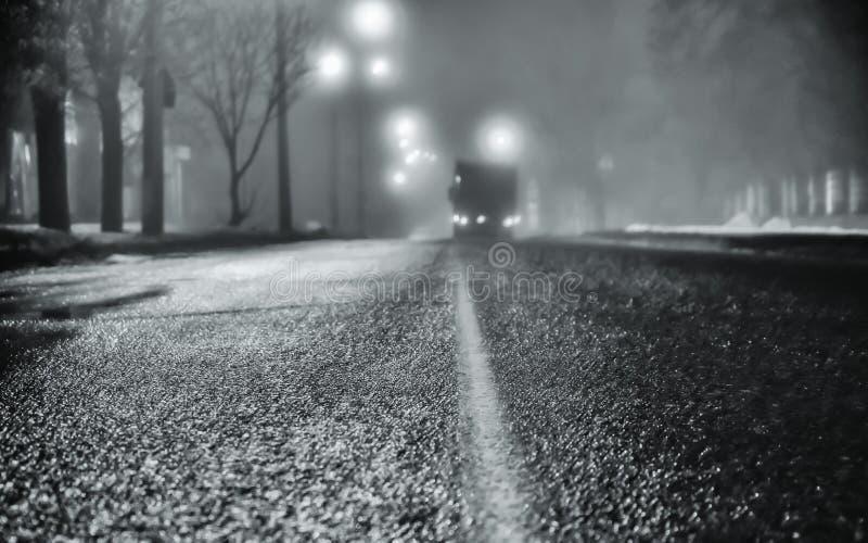 Dimma på gatorna av nattstaden Asfaltera vägen och bilen i dimma våt asfalt, farlig hal väg i vintersäsongen Stre royaltyfria bilder