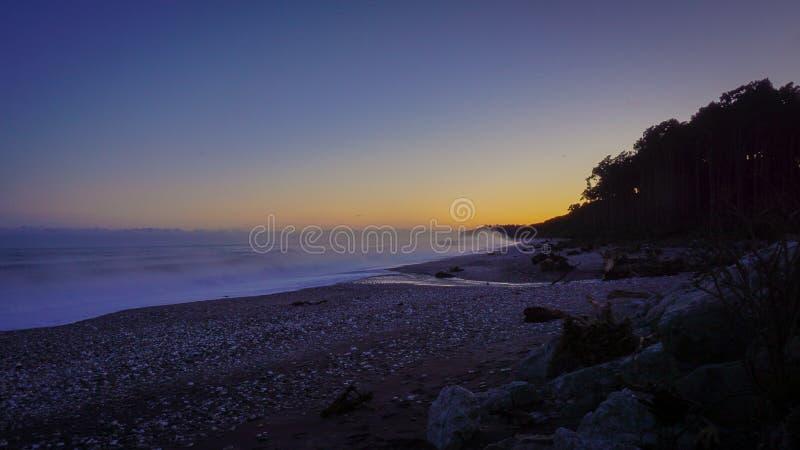 Dimma på soluppgång på stranden arkivfoto
