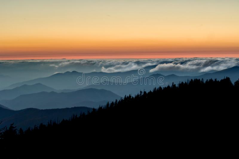 Dimma rullar in nedanför färgrik solnedgång i den rökiga Moutnainsen royaltyfri bild