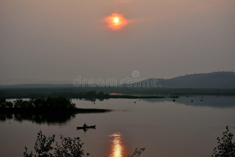 Dimmig afton på sjön med en fiskare i ett fartyg med reflexion av skogen och solen royaltyfria bilder