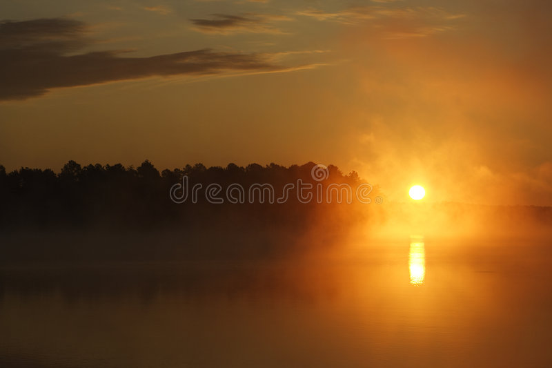 dimmig lakesoluppgång royaltyfria foton