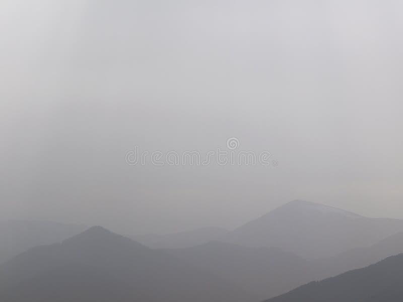 Dimmig morgon för bakgrund på berghorisonten Dimmiga försiktiga konturer av forested kullar i avståndet efter regn arkivfoto