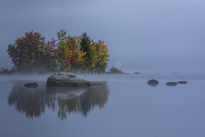 Dimmig sjö - ön med färgrika träd - höst/nedgång - Vermont royaltyfri bild