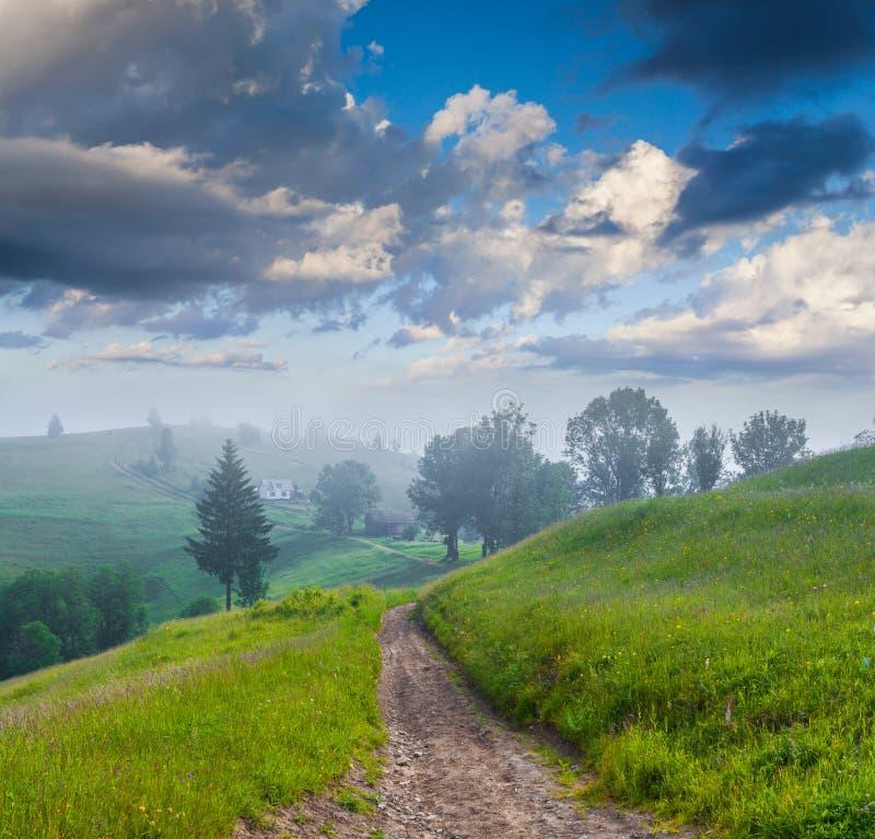 Dimmig sommarmornnig i bergby royaltyfria bilder