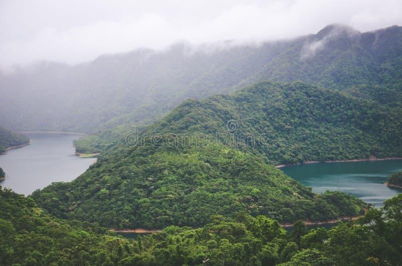Dimmigt landskap vid tusen ö sjö i Taiwan, Asien Sjö i dimma som omges av den tropiska skogen, lynnigt väder för rainforest arkivbild