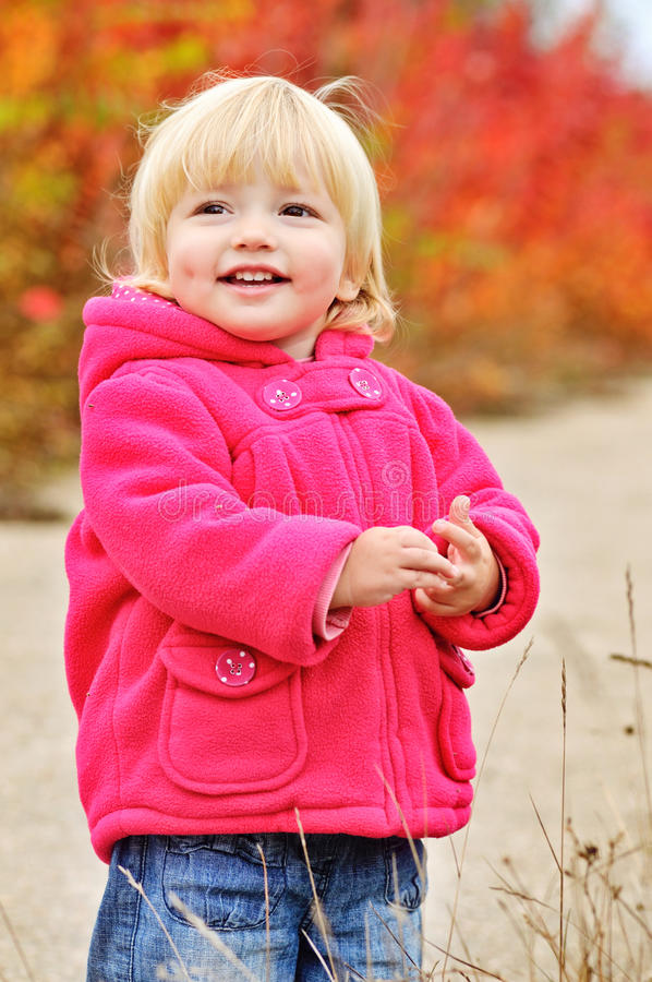 Dimple smile. Cute laughing toddler girl in fall park royalty free stock photo
