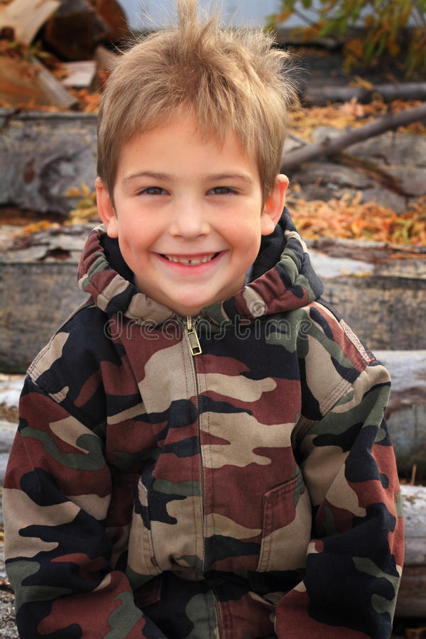 Dimples and Camo. Typical elementary school boy with blond hair and dimples wearing a camouflage coat sitting on a pile of logs royalty free stock photography