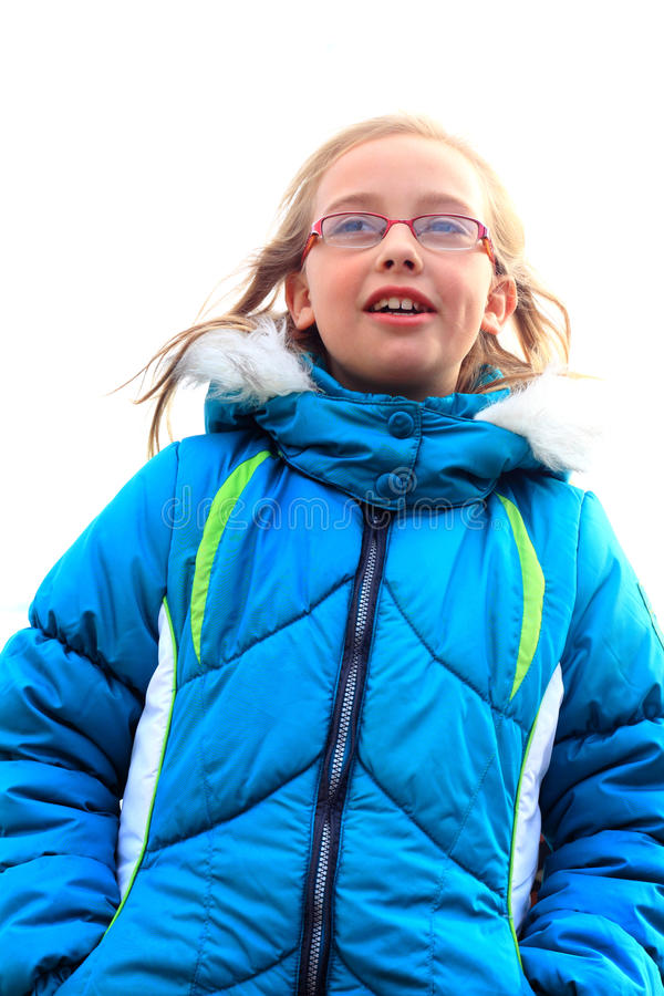 Dimples, Glasses and a Hoody. A smile and dimples on a cute little blond 9 year old girl wearing glasses and a blue winter hoody coat looking off into the stock photo