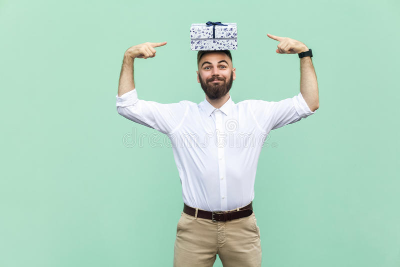 Din gåva på mitt huvud Fingrar den hållande gåvaasken för den roliga unga vuxna mannen på huvudet och att peka på asken royaltyfria bilder