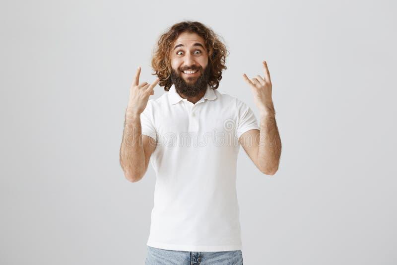 Din idé vaggar Studioskottet av den upphetsade och glade vuxna östliga mannen med skäggvisning vaggar tecken och att stirra på ka arkivfoton