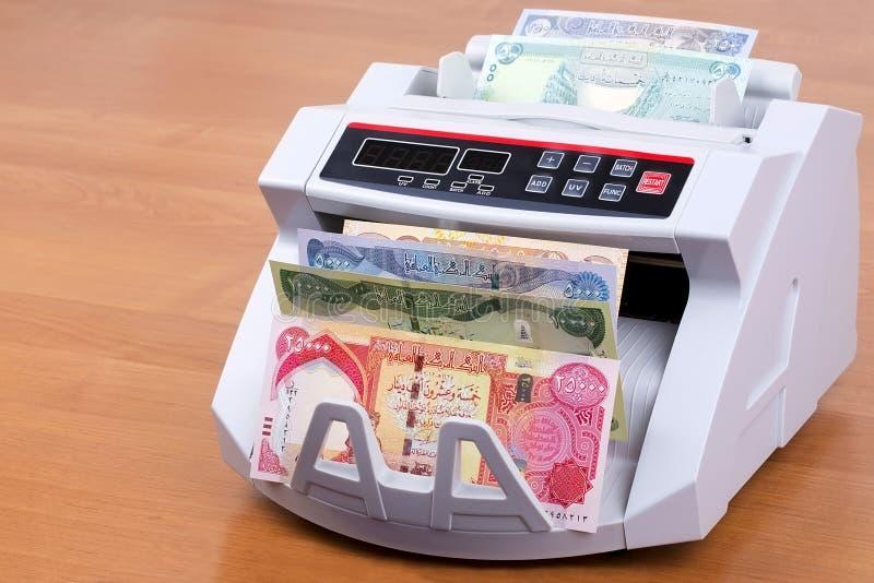 Dinar iraquiano em uma máquina de contagem imagem de stock