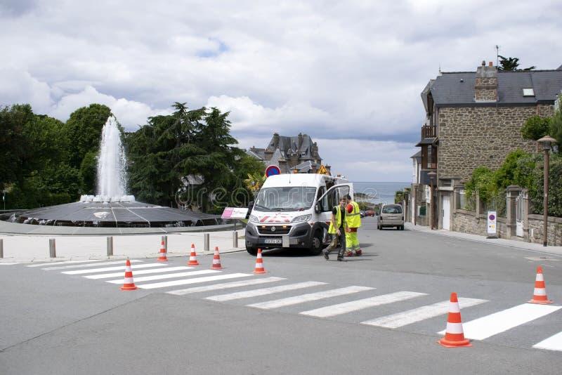 Dinard, France 15 juin 2019 Les travailleurs sur la rue près du véhicule d'entretien ont fraîchement peint le passage piéton piét photos libres de droits