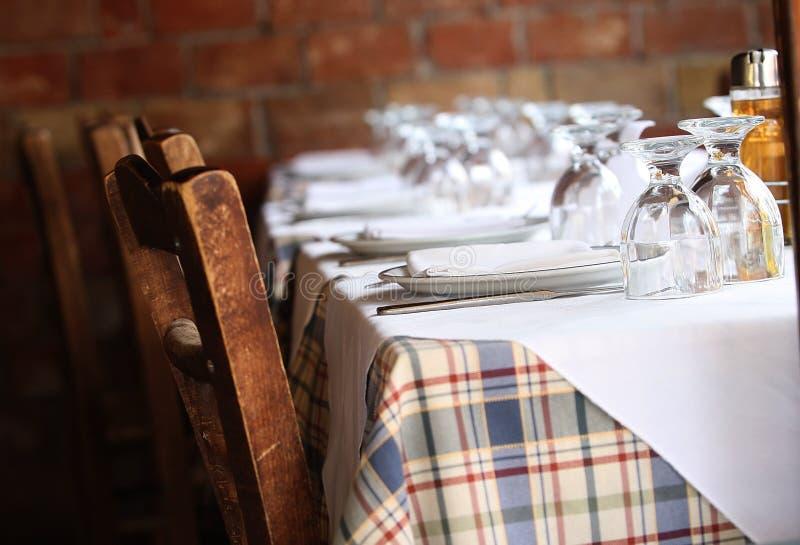 Dine framför ett soligt bord, på gott humör royaltyfri foto