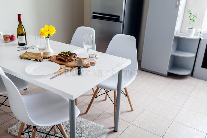 Diner die voor twee gediend in keuken plaatsen Modern keukenontwerp Geroosterd vlees met wijn in eetkamer stock foto's